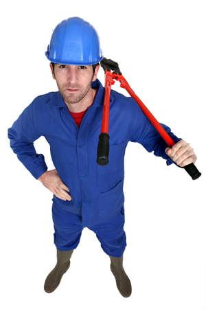 lumberman: Man carrying bolt-cutter over shoulder