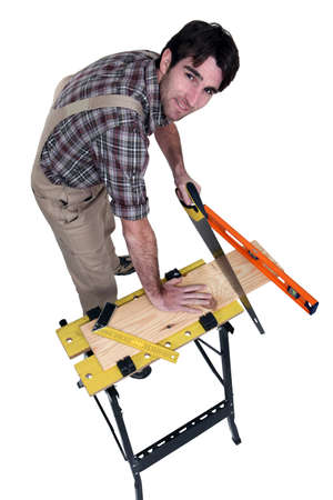 Carpenter sawing a plank photo