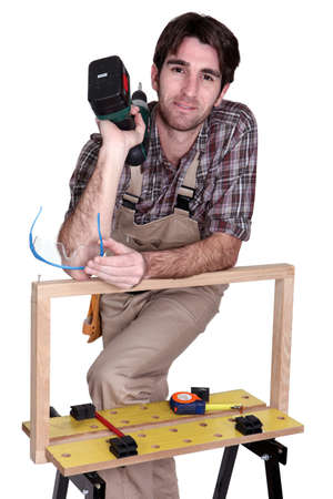 Man posing with his workbench and holding an electric screwdriver Stock Photo - 16951406