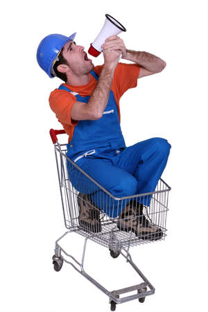Tradesman sitting in a shopping cart and yelling into a megaphone Stock Photo - 16951452