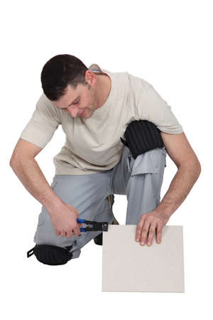 hinged: Man cutting tile to right size
