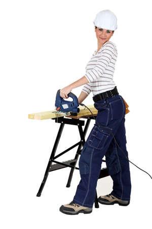 Woman using an electric saw Stock Photo - 17219202