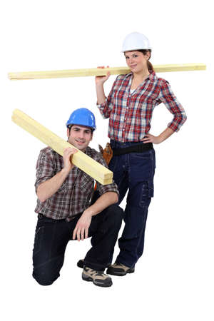 Labourers carrying wooden planks photo