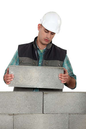 Bored tradesman laying cinder blocks photo