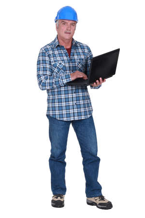 65 years old: Tradesman holding a laptop