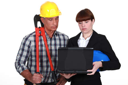 An architect and a foreman looking at a computer  photo