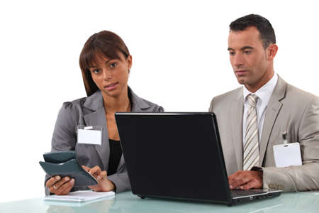 human resource affairs: Business couple  with a laptop and calculator Stock Photo