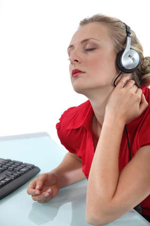 workplace wellness: Woman relaxing in front of computer listening to music