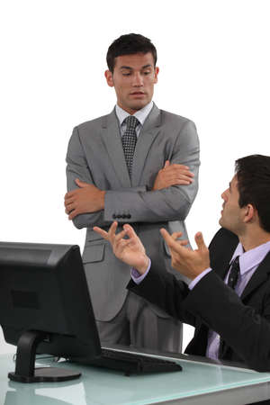 authoritative: Boss having a discussion with his defensive employee Stock Photo