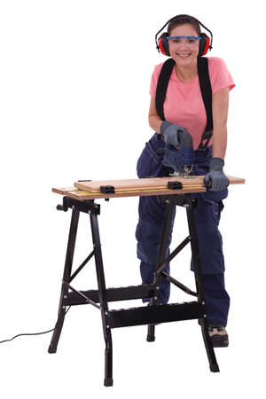Female capenter cutting plank with electric saw Stock Photo - 17214524