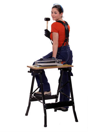 workwoman: Portrait of a tile fitter standing by a workbench and holding a mallet