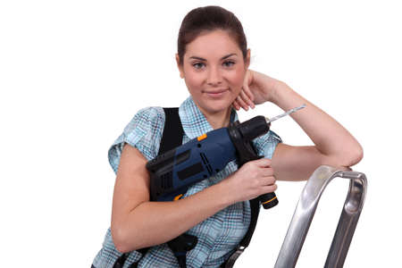 servicewoman: craftswoman working with a drill
