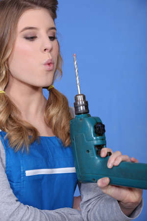 craftswoman pretending that her drill is a gun photo