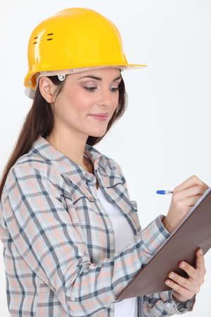 female construction worker: craftswoman holding a notepad and writing