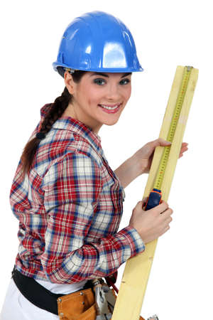 Construction worker measuring a piece of wood photo