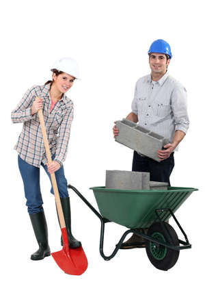 hard working people: female bricklayer with shovel and male counterpart
