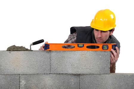 trussing: artigiano muratore che lavora con un livello di Archivio Fotografico