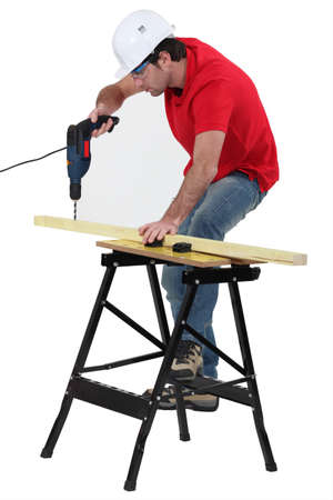 Carpenter drilling into wooden plank photo