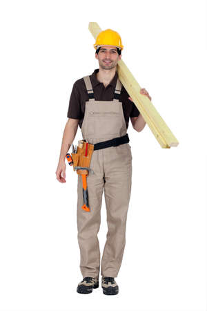 unskilled worker: A builder carrying wooden planks Stock Photo