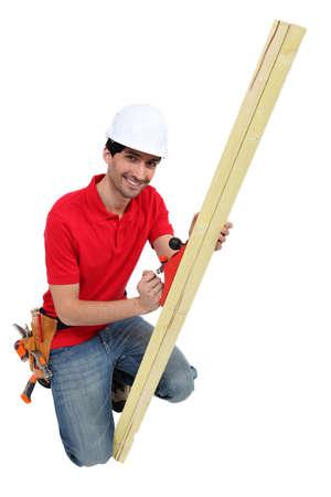 whittle: Man using wood plane whilst kneeling Stock Photo