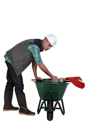 bending over: Labourer placing his tools in a wheelbarrow Stock Photo