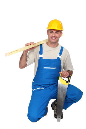 serrucho: Un carpintero se arrodill� con un serrucho Foto de archivo