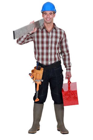 tradesperson: Worker carrying an aluminium plank and a toolbox