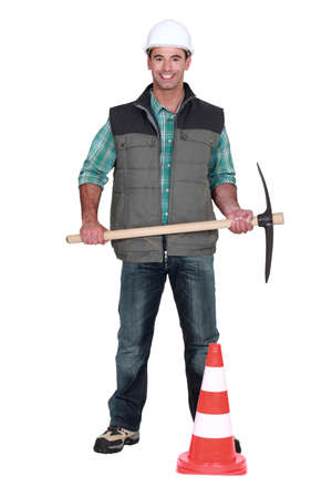 Man with pick-axe and traffic cone photo