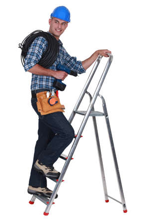 power operated: A tradesman climbing a stepladder Stock Photo