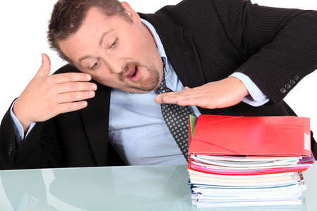 Businessman with a pile of paperwork photo