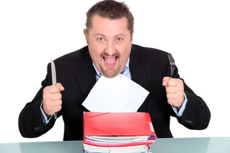 devouring: Businessman devouring a pile of paperwork Stock Photo