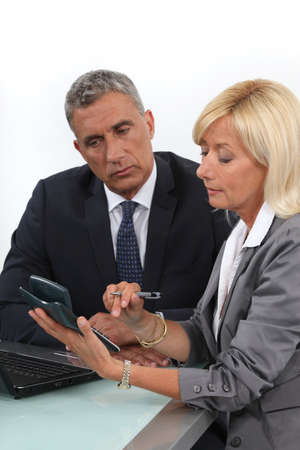 Mature business couple with a  calculator photo