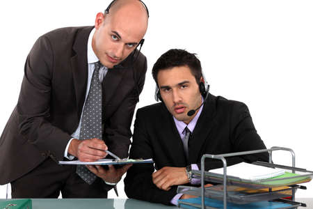 two businessmen at the office wearing headsets photo