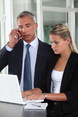 business woman phone: Boss and personal assistant preparing for meeting
