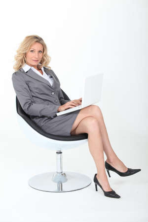 Confident woman sitting in an armchair photo