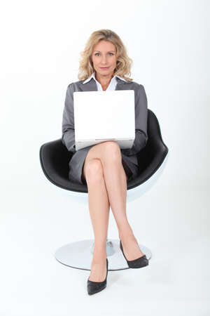 smug: Businesswoman sat in modern chair with laptop computer