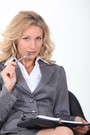 Blond woman chewing pen photo