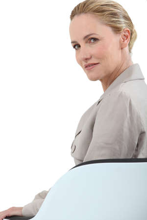late thirties: Blonde businesswoman sitting in a chair