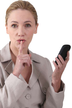 Woman indicating quiet whilst holding a phone photo