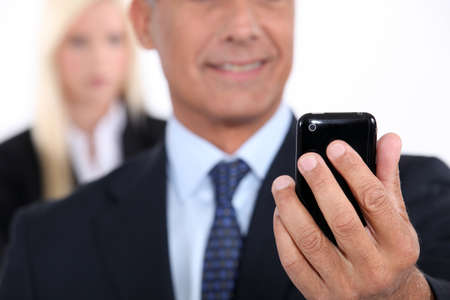 Man using a cellphone with his assistant in the background Stock Photo - 17220020