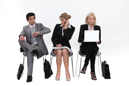 file d attente: Les gens d'affaires assis dans une rang�e Banque d'images