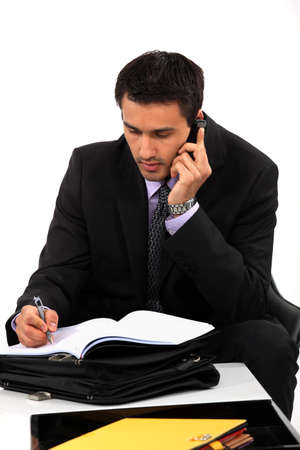 taking notes: Businessman taking notes during important call