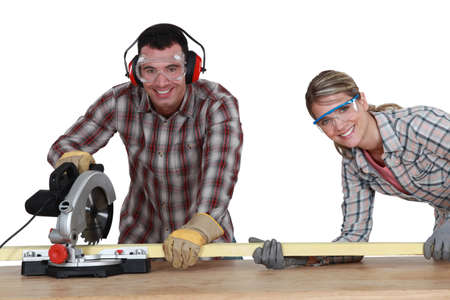 Couple using circular saw photo