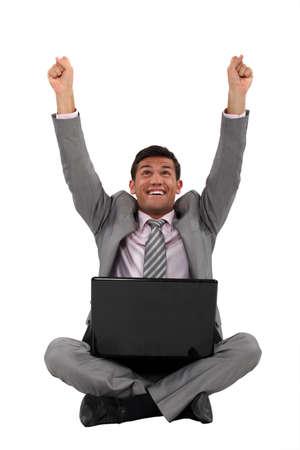 Excited businessman sat cross-legged on the floor photo