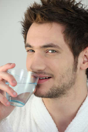 Man drinking a glass of water photo
