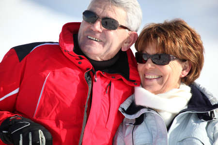 Middle-aged couple on a snowy mountain photo