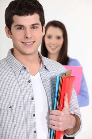 all smiles: young student all smiles holding files and girl in background