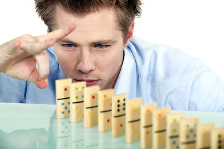 rally finger: Businessman flicking dominoes