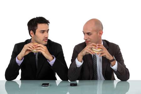 Two businessmen sat eating hanburgers Stock Photo - 17219753