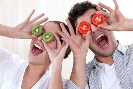 hand covering eye: Covering his eyes with a couple slices of kiwi and tomato